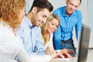 gemeinschaftliche Arbeit von vier Menschen an einem Laptop
