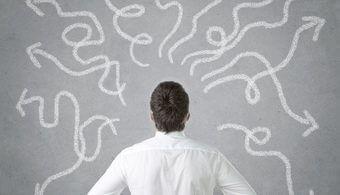 Mann vor einer Wand voller unterschiedlicher Wege - Karrierecoach - passendes Studium