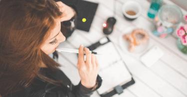 Frau sitzt nachdenklich am Tisch vor einem Notizbuch