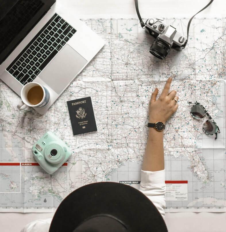 Auslandssemester Frau zeigt auf Weltkarte auf der PC Reisepass Kamera sind