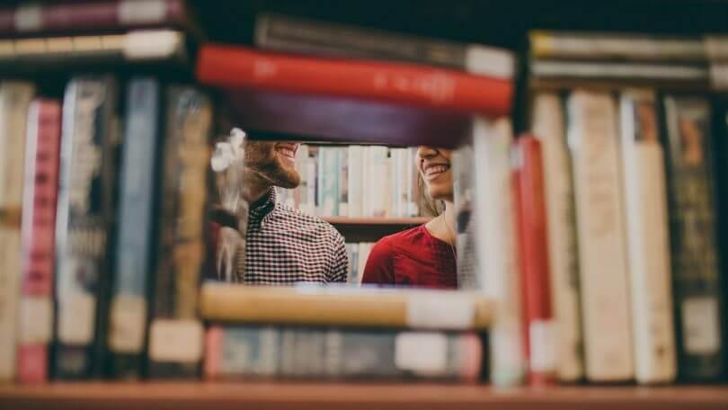 Blick durch Bücherregal auf zwei Personen