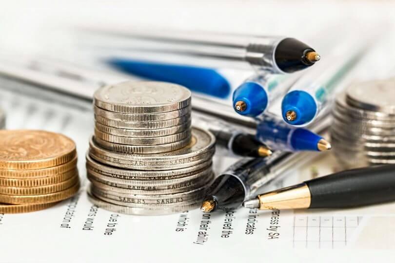 Münzen und Stifte liegen auf einem gedruckten Dokument