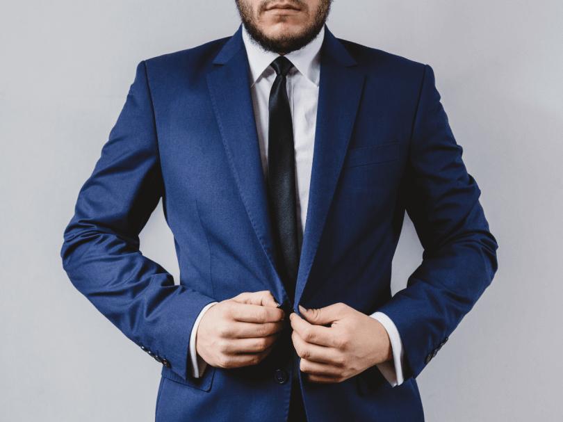 Mann mit schickem Anzug, weißem Hemd und Krawatte