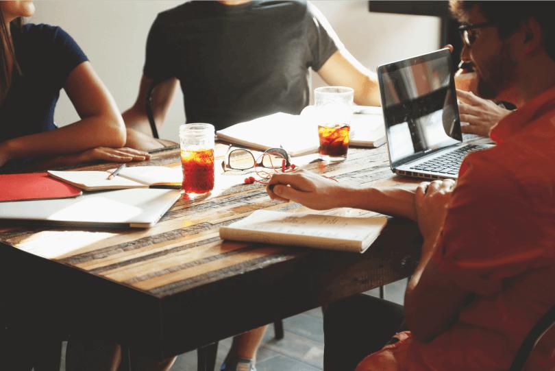 Arbeitnehmer sitzen zusammen am Tisch und arbeiten gemeinsam
