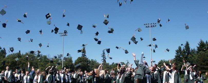 Studiumsabsolventen schmeißen ihre Doktorhüte in die Luft