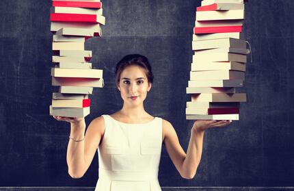 Frau jeweils einem großen Stapel Bücher auf jeder Hand