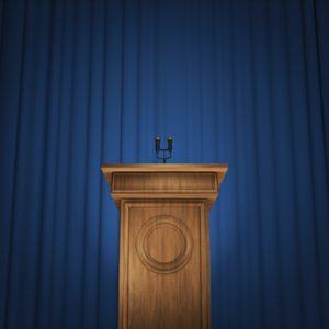 Rednerpult vor einem blauen Vorhang