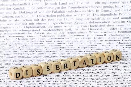 Eine Reihe aus Buchstaben gelegt mit Würfeln, die das Wort Dissertation bildet - Doktortitel