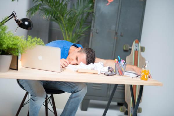 Mann gelangweilt am Schreibtisch
