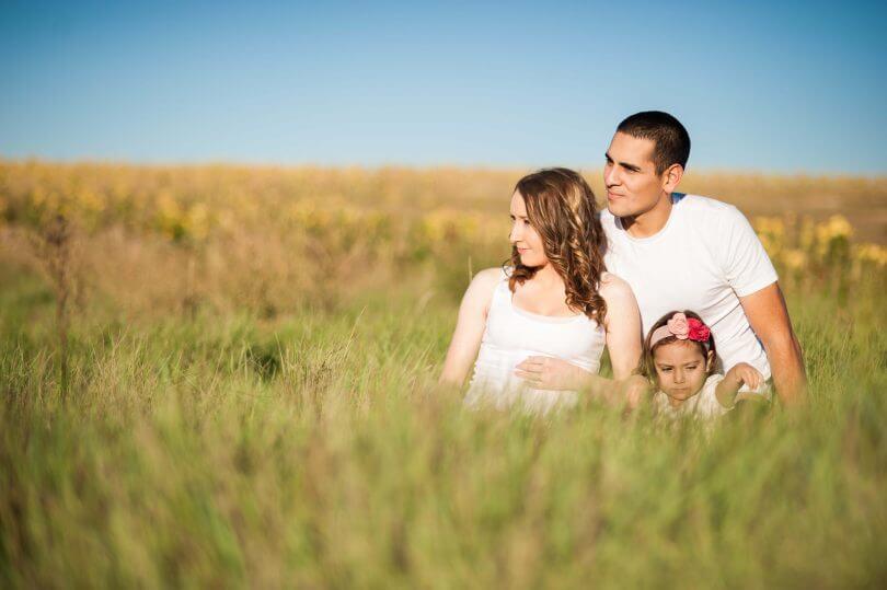 Familie mit Kind sitzt im Gras