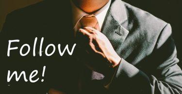"""Mann fasst sich an Krawatte, Schriftzug """"Follow me!"""""""