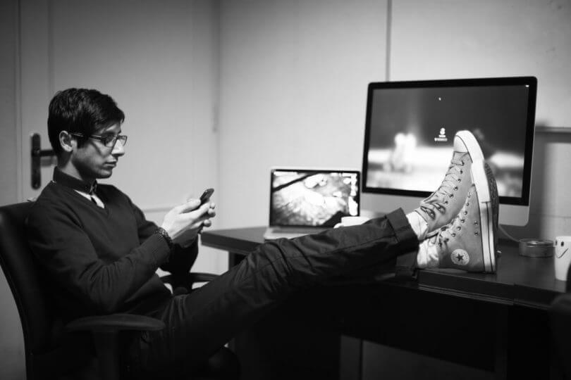 Manieren im Beruf und Gerüchte: Mann mit Smartphone