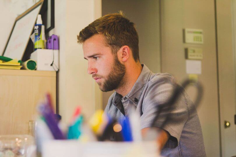 Mann sitzt konzentriert am Schreibtisch