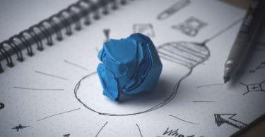 zerknülltes Papier auf Zettel mit Kritzeleien - symbolisiertes Gedankenwirrwarr
