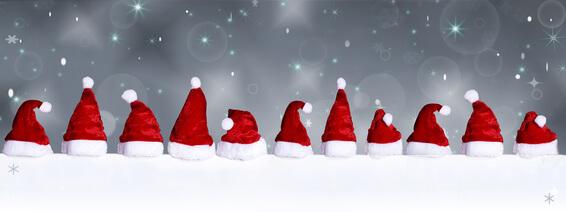 Viele Weihnachtsmützen auf einer schneebedeckten Fläche