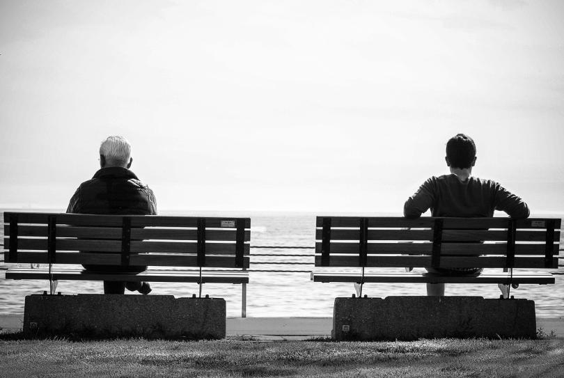 junger und alter Mann sitzen auf zwei Bänken
