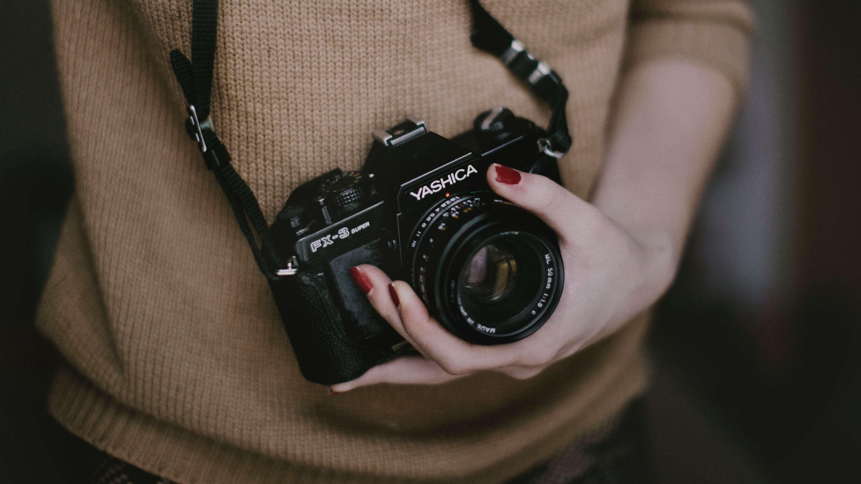 Mädchen mit Kamera vor dem Bauch