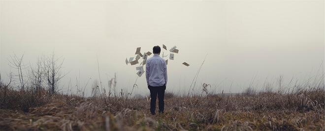 Mann vor fliegenden Papierfetzen