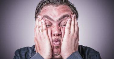 Mann mit zwei Händen am Gesicht - Diätfrust - Diät auf der Arbeit