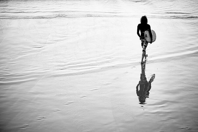 Schwarz weiß Bild von einem Surfer als Sinnbild des Work and Travel Nutzers