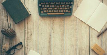 Schreibtisch mit Schreibutensilien, Brille und Deko - fertig für das Schreiben englischer Unterlagen