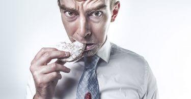 Mann beißt in Keks und bekleckert Krawatte