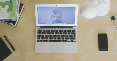Laptop, Lehrbücher, Stifte, Notizbuch auf Schreibtisch
