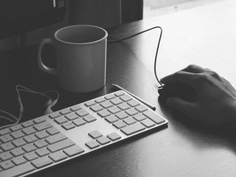 Tastatur, Maus und Kaffeetasse auf Schreibtisch