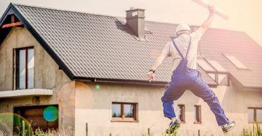 Bauarbeiter hüpft vor einem Haus