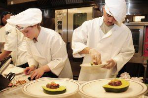 Zwei Kochaushilfen beim Anrichten der Speisen