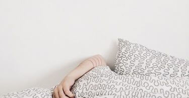 Frau liegt unter der Decke - Prokrastination