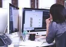 Frau am Schreibtisch vor Computer