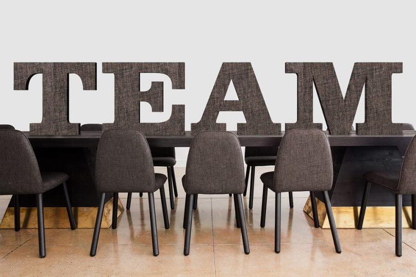 Tisch mit Stühlen, auf dem Tisch großer Schriftzug TEAM