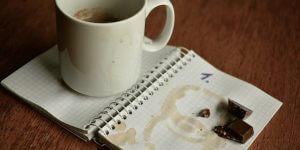 Kaffeetasse und Schokolade auf Notizbuch