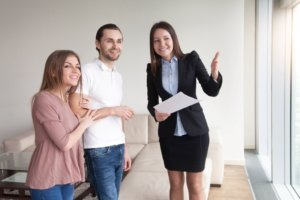 Maklerin mit Kunden bei Wohnungsbesichtigung
