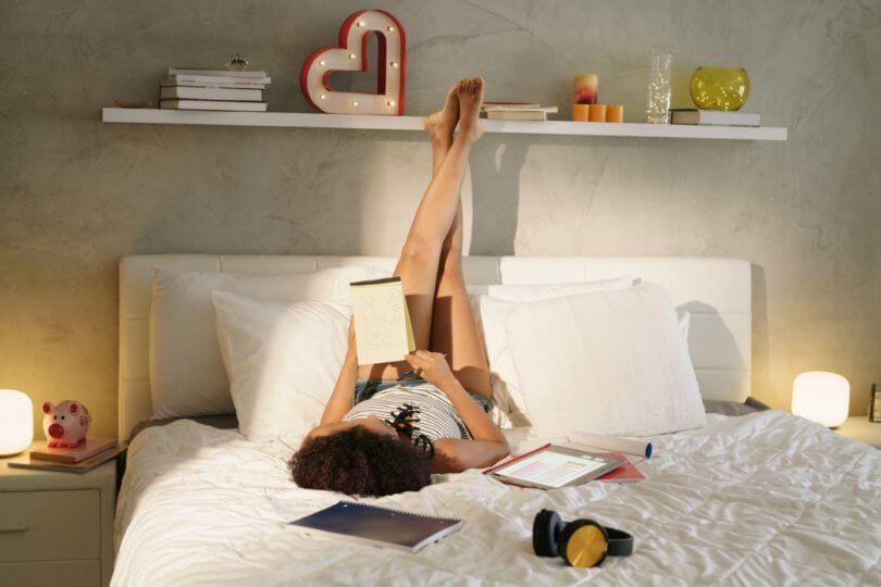 Frau liegt auf dem Bett in eigener Wohnung