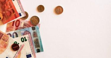Euroscheine und Münzen auf weißem Hintergrund