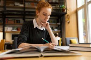 Rothaarige Studentin lernt über Büchern in der Bibliothek einer Hochschule oder Universität