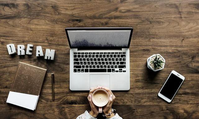 Erfolgreiches Praktikum Tisch mit Laptop, Handy, Buch, Kaffeetasse