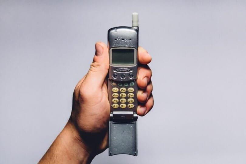 Erreichbarkeit Feierabend Handy wird von Hand gehalten