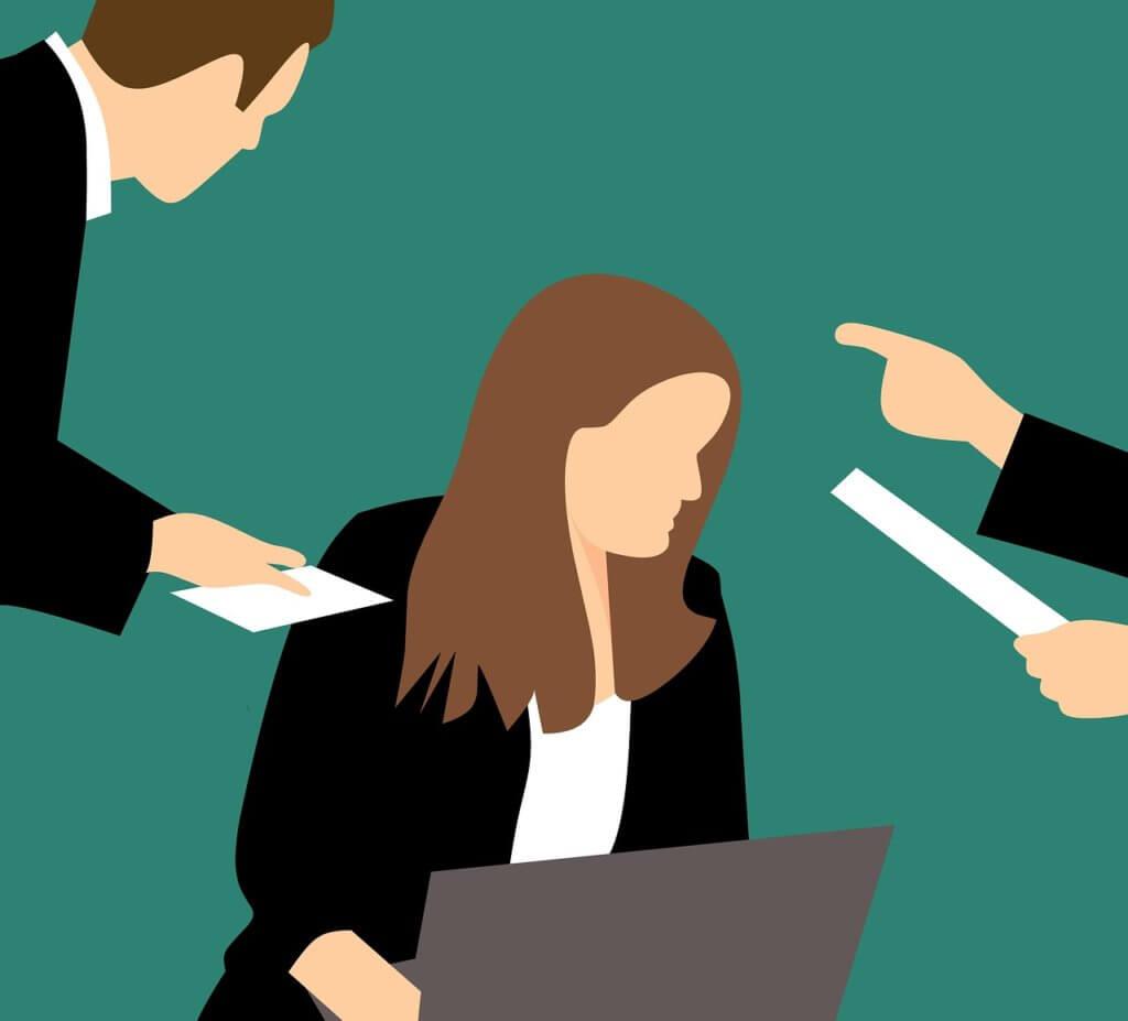 Mobbing - Frau am Arbeitsplatz wird angemeckert