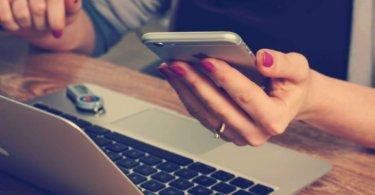 Xing-Profil Optimieren Frau mit Smartphone in der Hand sitzt vor einem Laptop
